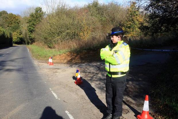 An officer at the scene in Horns Lane yesterday