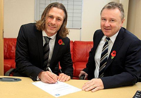 Gareth Ainsworth signs the contract that will keep him as Wanderers manager until the end of the season, watched by chairman Don Woodward