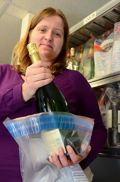 Buckinghamshire County Council Trading Standards Officer Donna Ward bags up a bottle of counterfeit champagne.