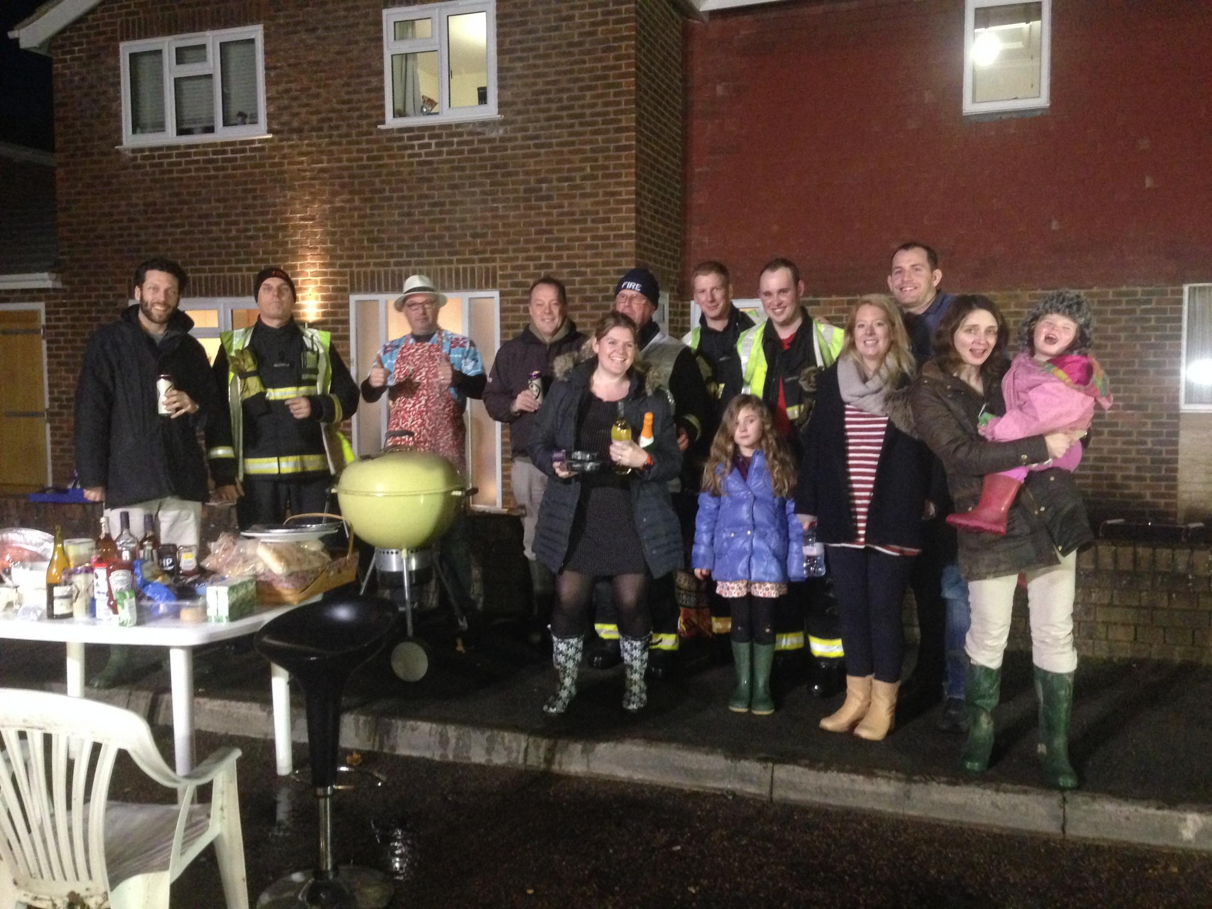 Firefighters enjoying a well-earned bite to eat as Garnet Court residents lay on a barbeque. Pic courtesy of David James