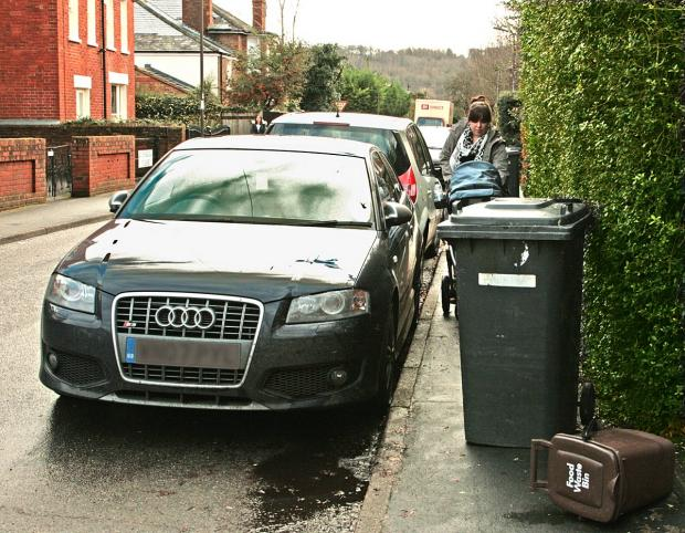 A mother with her young child finds her way blocked off by recently collected bins on Glade Road.