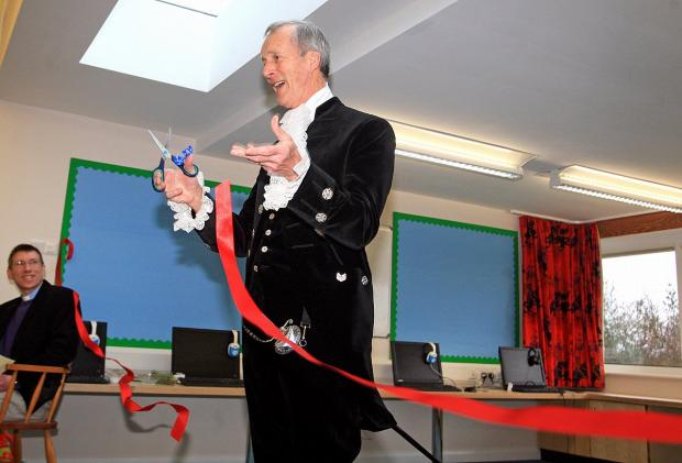 Sir Stuart Hampson cuts the ribbon