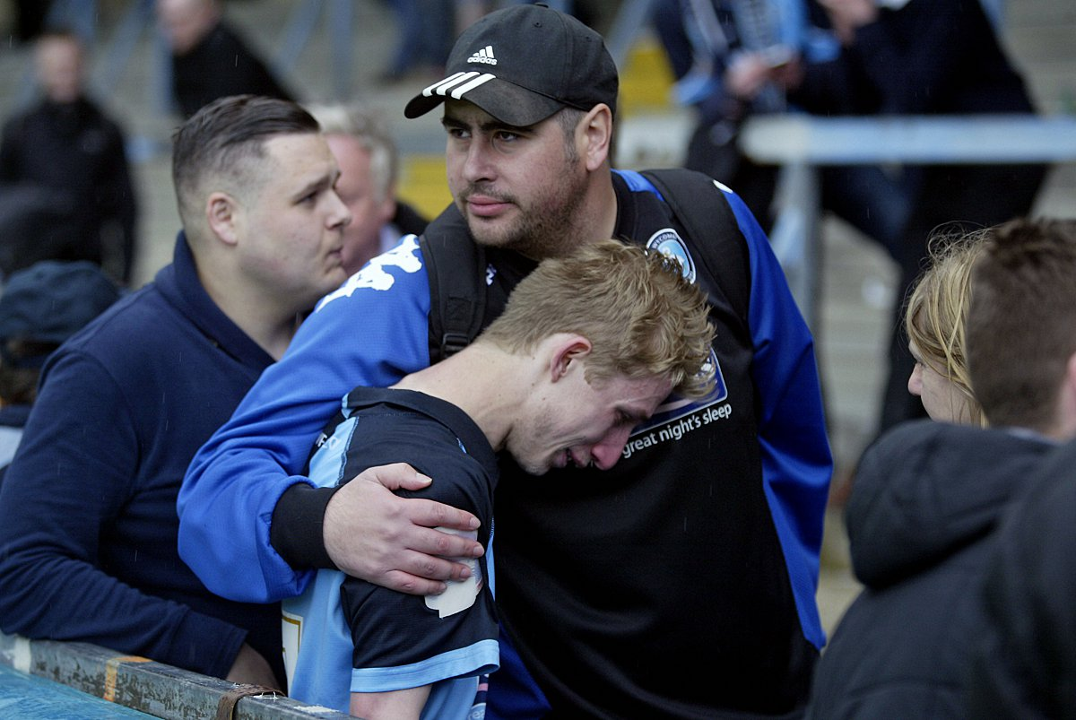 Wanderers fan Anwar Kritah comforts another supporter after their side's defeat by Bristol Rovers