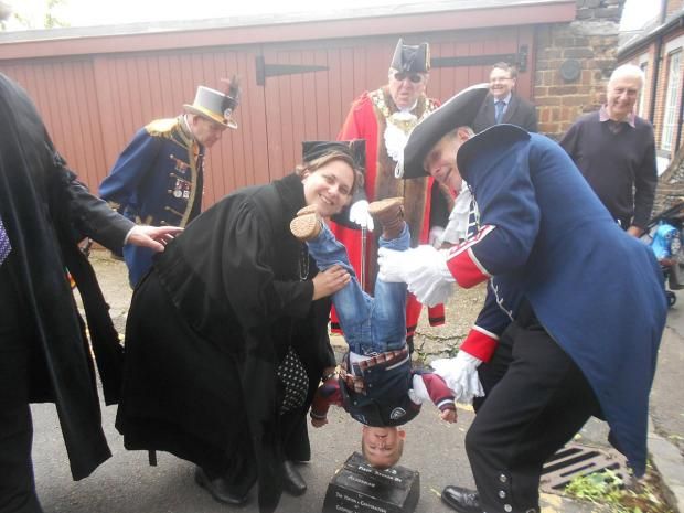 Deputy Mayor Paula Lee turns her son Dylan upside down with the help of town crier John Taylor