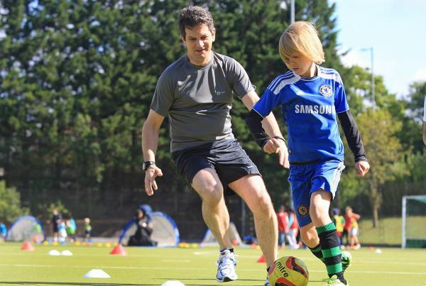 Steve Baker plays football with one of the youngsters