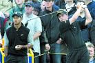 Taking on Tiger: Tiger Woods (left) watches Luke Donald tee off at the 2003 Open Championship