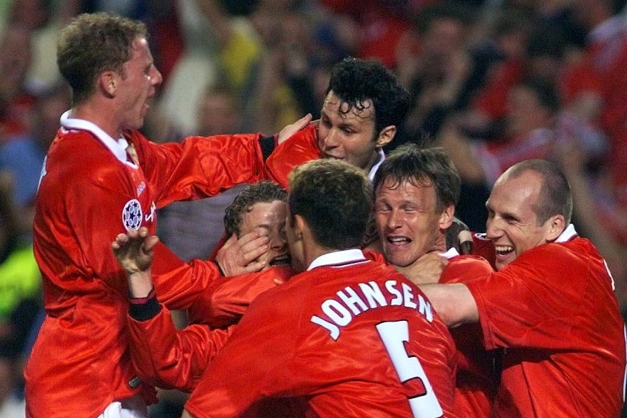 Solskjaer is mobbed by his team-mates after his Champions League final winner in 1999